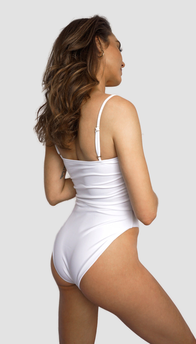 Carling Liski wears Canadian swimsuit brand Prairie Swim designed in Toronto. Simple white straight-cut neckline one piece swimsuit with figure flattering cinched waist, adjustable straps and high cut legs