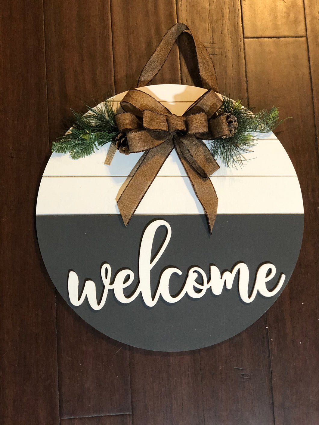 Welcome wooden door round hanger with bow and greenery