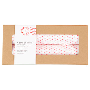 two organic muslin swaddles for babies with red kiss pattern