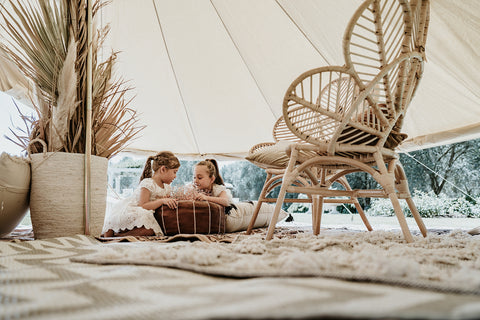 Two flower girls playing inside a boho themed teepee. Cane furniture, leather moroccan ottomans, rattan baskets filled with dried floral arrangements.