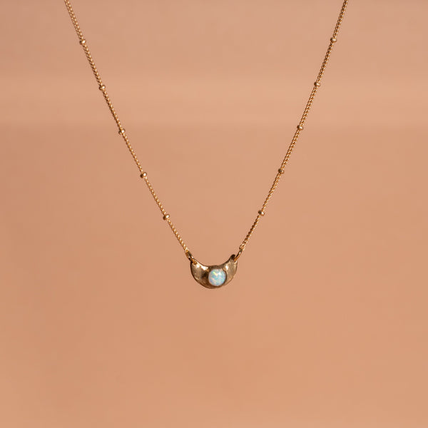 shiny gold toned Iron Oxide dainty moon necklace set with an opal gemstone