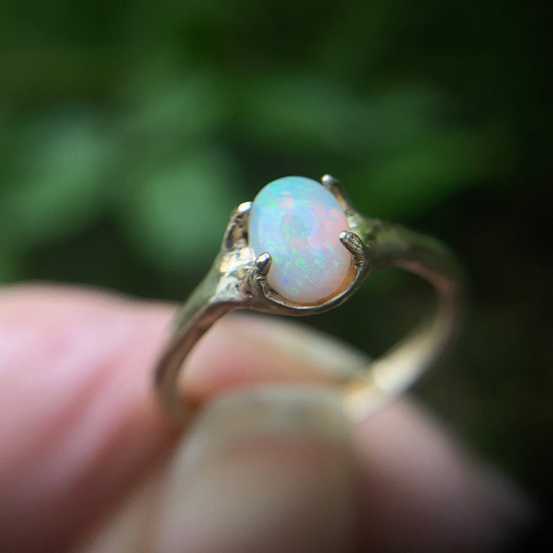 Close up of gold tone bronze ring set with an ethically sourced opal in a classic setting by Iron Oxide Designs
