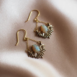 Gold Tone bronze earrings in the shape of beams of light set with teardrop shaped, lab grown opals on a pink satin background