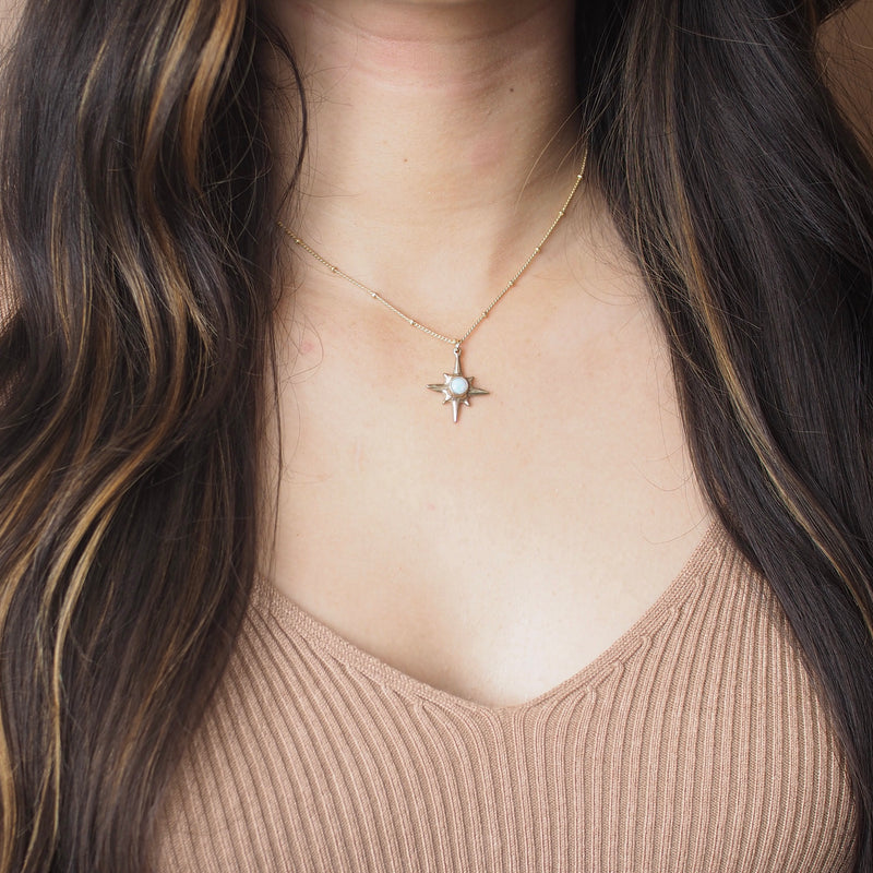 Shiny gold Iron Oxide North Star Polaris Necklace on body
