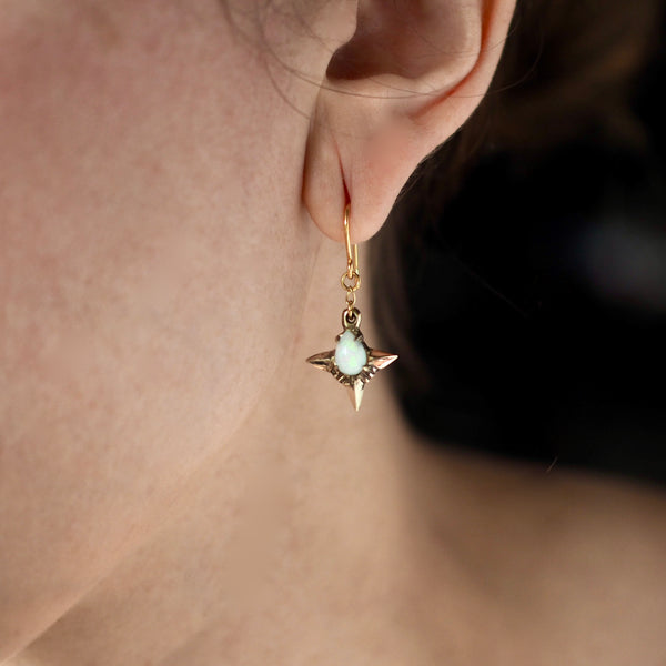 Teardrop shaped lab grown opal set in 4 point star setting in gold tone bronze handmade by Iron Oxide Designs on a model