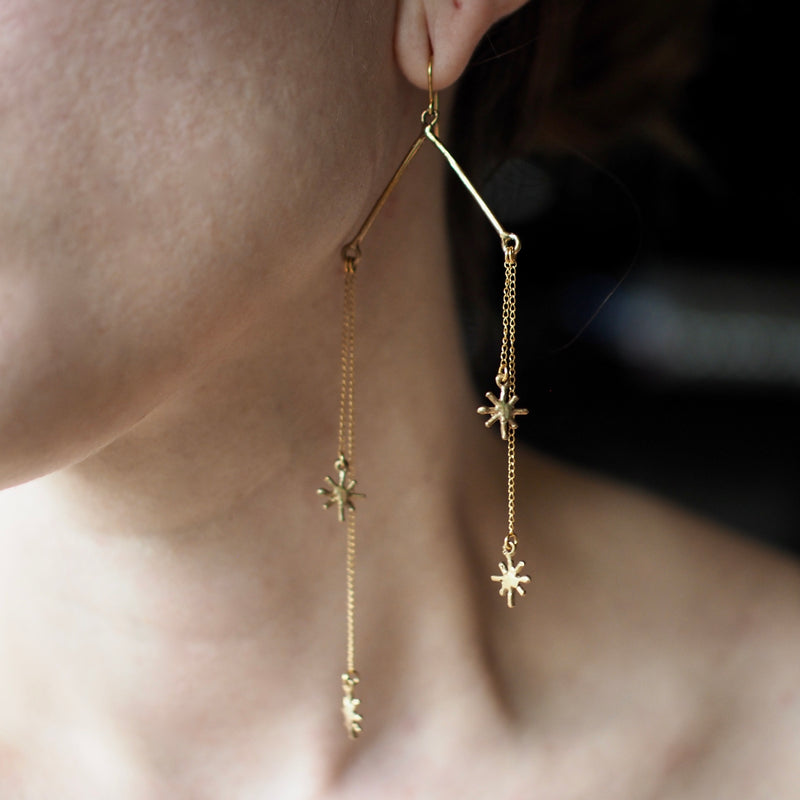 Falling star chain earrings with glitter motifs by Iron Oxide Designs on a model