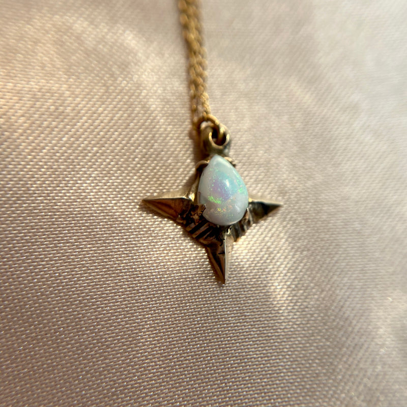 Close up of Teardrop shaped lab grown opal set in a four point star in gold tone bronze handmade by Iron Oxide Designs