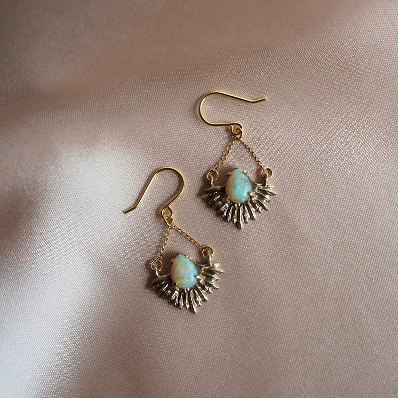 Gold Tone bronze earrings in the shape of beams of light set with teardrop shaped, lab grown opals.