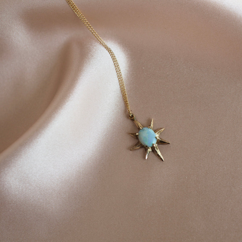 Close up of Supernova large star necklace set with lab grown opal in gold tone bronze