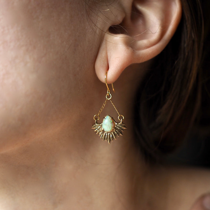 Gold Tone bronze earrings in the shape of beams of light set with teardrop shaped, lab grown opals on a model for scale