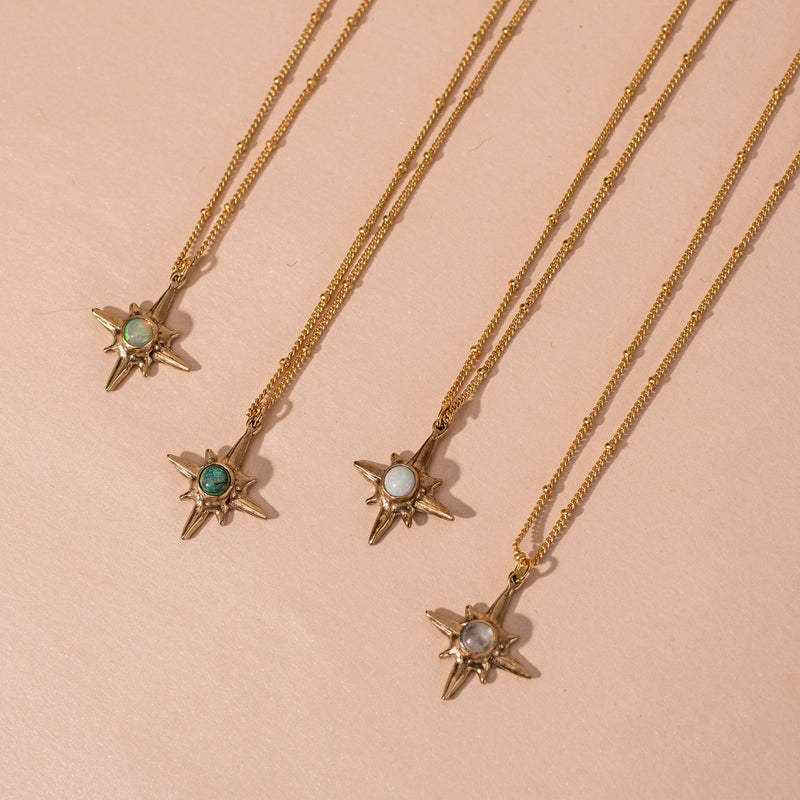 Collection of Shiny gold Iron Oxide North Star Polaris Necklaces set with gemstones