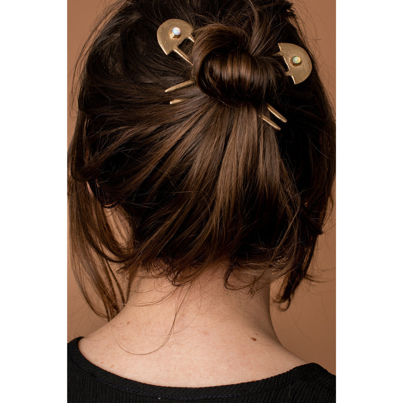 Two brass  Iron Oxide hair sticks in a messy bun
