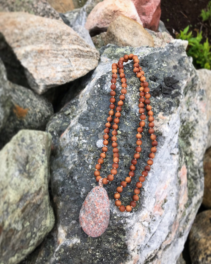 Nordic Love Mala in Sandalwood with a gurubead  on a beach in Scandinavia