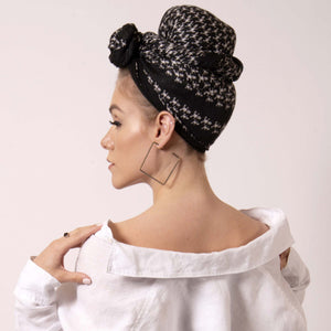 Make a statement and transform ärtskül's iconic black and white Baby Pop, Nana Rectangle scarf into a chic turban. Express your personality and style with a few creative ties and twists that can make a challenging hair day a thing of the past. The scarf features the reimagined houndstooth pattern with the baby icon. Adds a nice touch of attitude to any outfit.