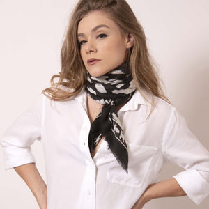 Artskul's Baby Pop Large Square Cashmere Blend Scarf. The black and white scarf adds a touch of edgy sophistication. Twist,  wrap and tie this large square into an oblong shape to create a polished look.  ärtskül's remixed houndstooth pattern captivates the eye while paying homage to the classic print with a twist of the unexpected.