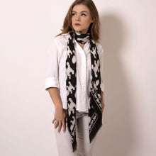 Load image into Gallery viewer,  Artskul's Baby Pop Large Square Cashmere Blend Scarf can be styled with a choker drape effect.  This black and white scarf is lusciously soft and easy to style in so many different ways. This scarf is made in Italy from the most luxurious fabric with hand fringed edging.  ärtskül's remixed houndstooth pattern captivates the eye while paying homage to the classic print with a twist of the unexpected.