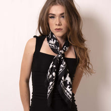 Load image into Gallery viewer, Hey Pretty baby. There are many possibilities to style a square scarf and Artskul's Baby Pop Medium Square Scarf  in black and white can elevate any look. With a simple fold and roll, this scarf can be tied in a number of ways to create an artistic statement that adds character and personality to your style.