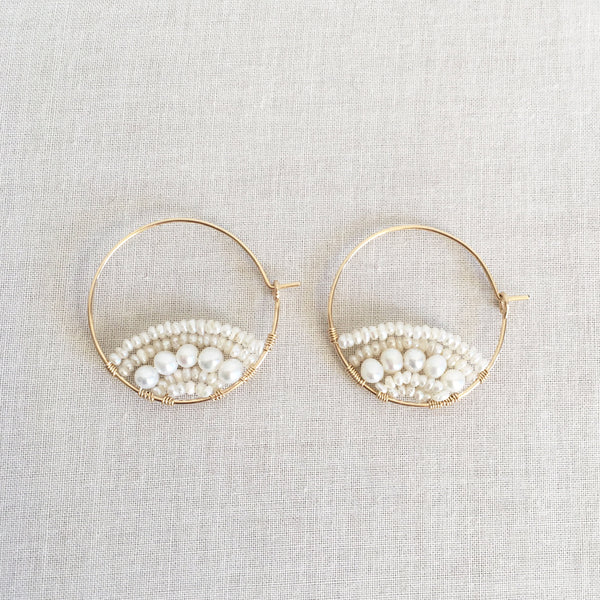 this is a pair of unique pearl hoop earrings