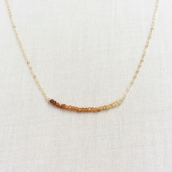 This cute ombre necklace is made of shaded garnet bead from dark to light orange color on a dainty gold chain.