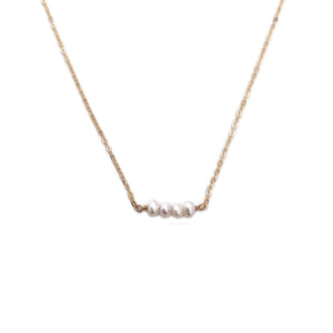 The dainty pearl bead necklace is simple and dainty.  It's made of 14k gold chain with four fresh water pearl beads.