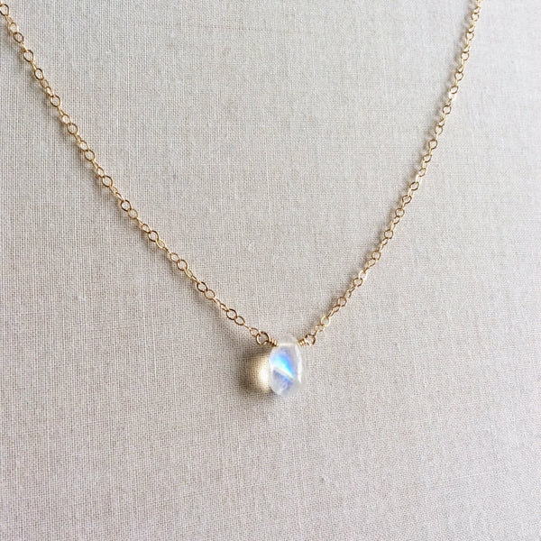 The dainty moonstone necklace that we make features a single genuine moonstone and is attached to a 14k gold, gold fill or sterling silver chain.
