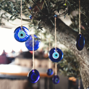 Blue evil eye amulets hanging on a tree