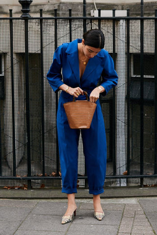 Woman wearing a classic blue jumpsuit and holding a small brown bucket bag