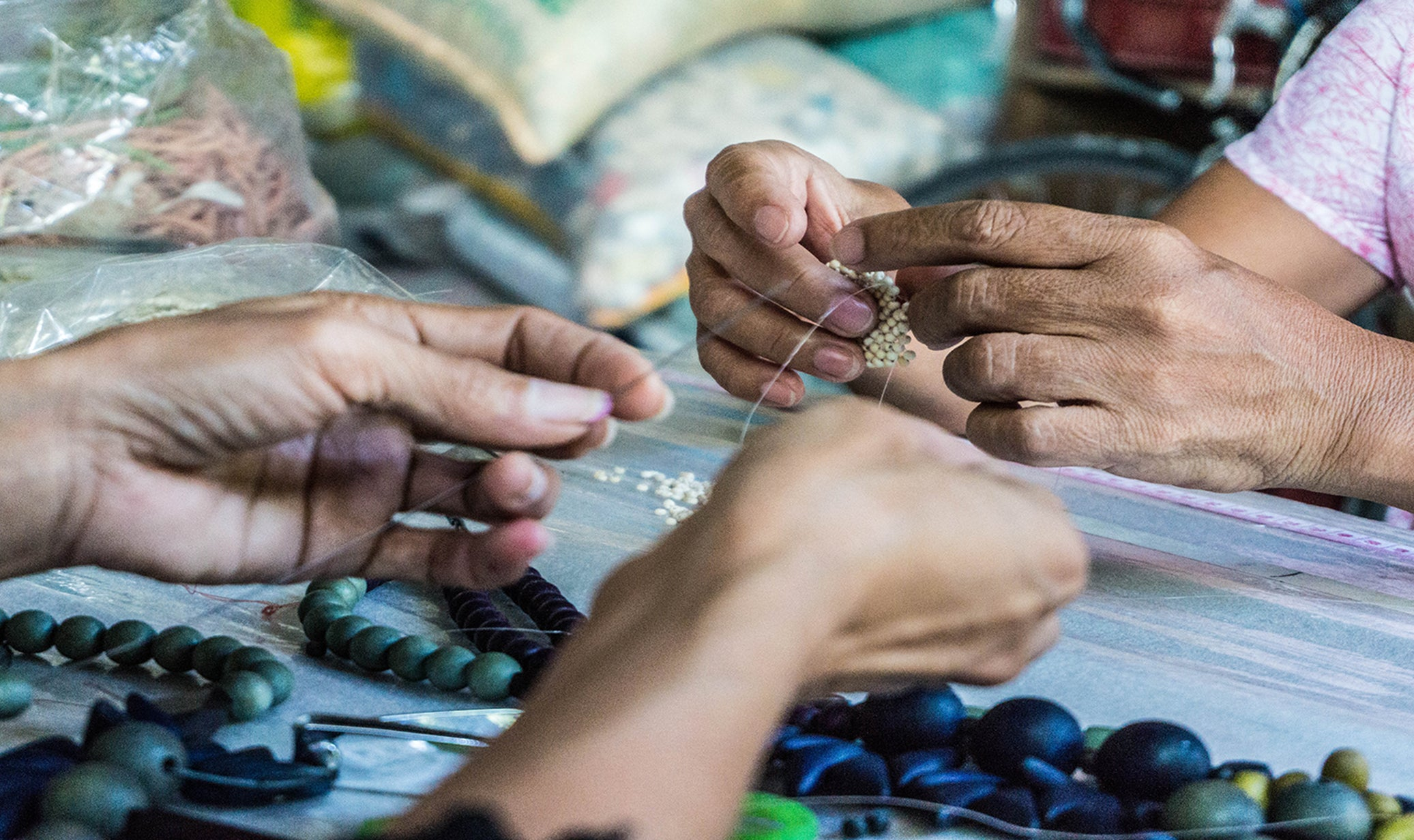 Artisans working on wooden necklaces and bracelets