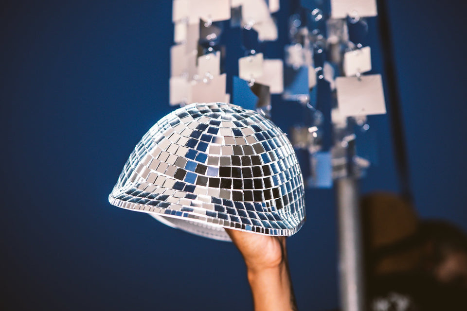 Up-close view of the Thousand Deep disco ball hat, being hoisted towards the sky. Front-facing view of the hat. Photo taken on rooftop at Lightning Society in Brooklyn, New York