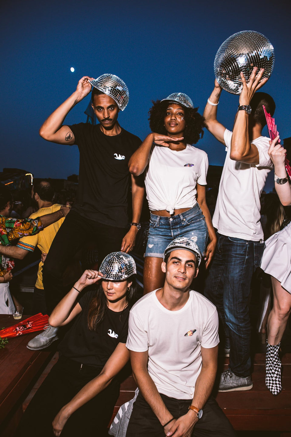 Male and female models all wearing the Thousand Deep disco hat, dancing to music with a disco ball. Photo taken on rooftop at Lightning Society in Brooklyn, New York