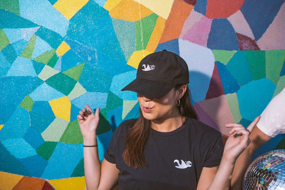 Female model wearing a Thousand Deep flying squirrel black dad hat while dancing. Front-facing view of hat. Photo taken on rooftop at Lightning Society in Brooklyn, New York