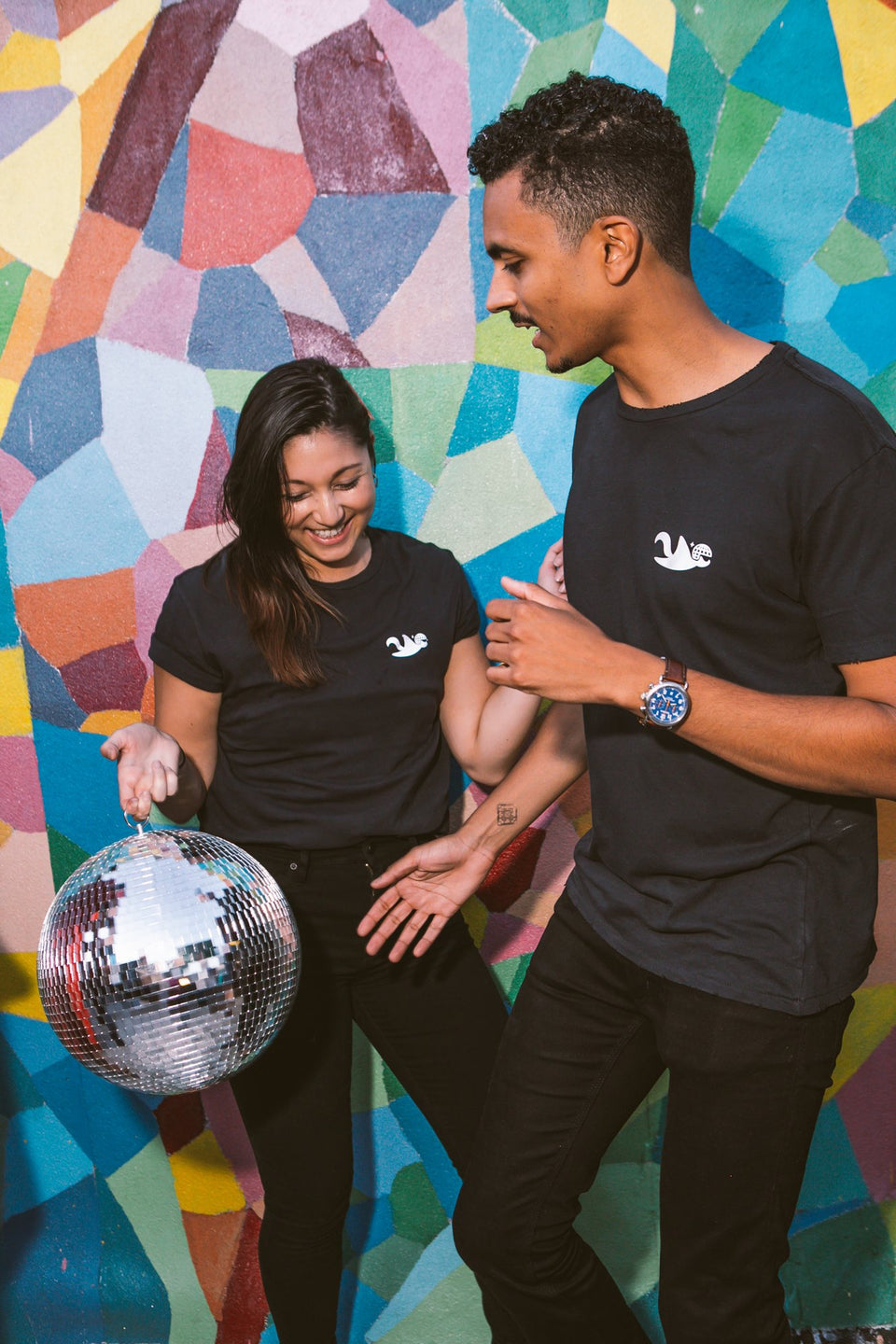 Male and female model together wearing a Thousand Deep flying squirrel reflective black shirt. Models are dancing and holding a disco ball. Photo taken on rooftop at Lightning Society in Brooklyn, New York