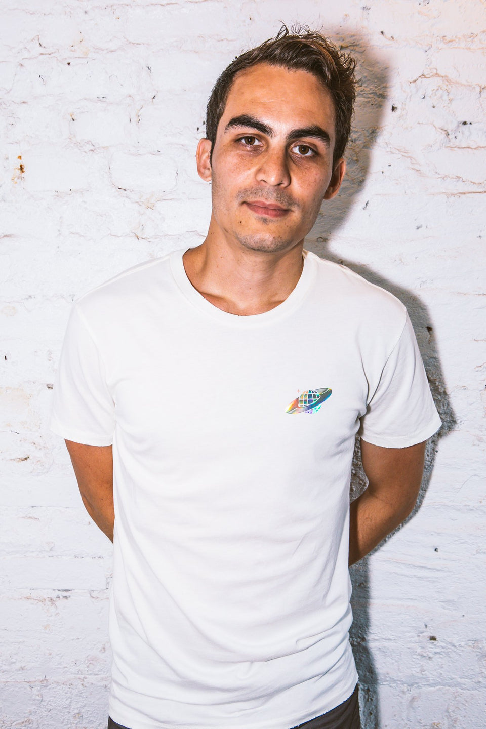 Male model wearing a Thousand Deep Planet Disco iridescent white shirt. Photo taken on rooftop at Lightning Society in Brooklyn, New York