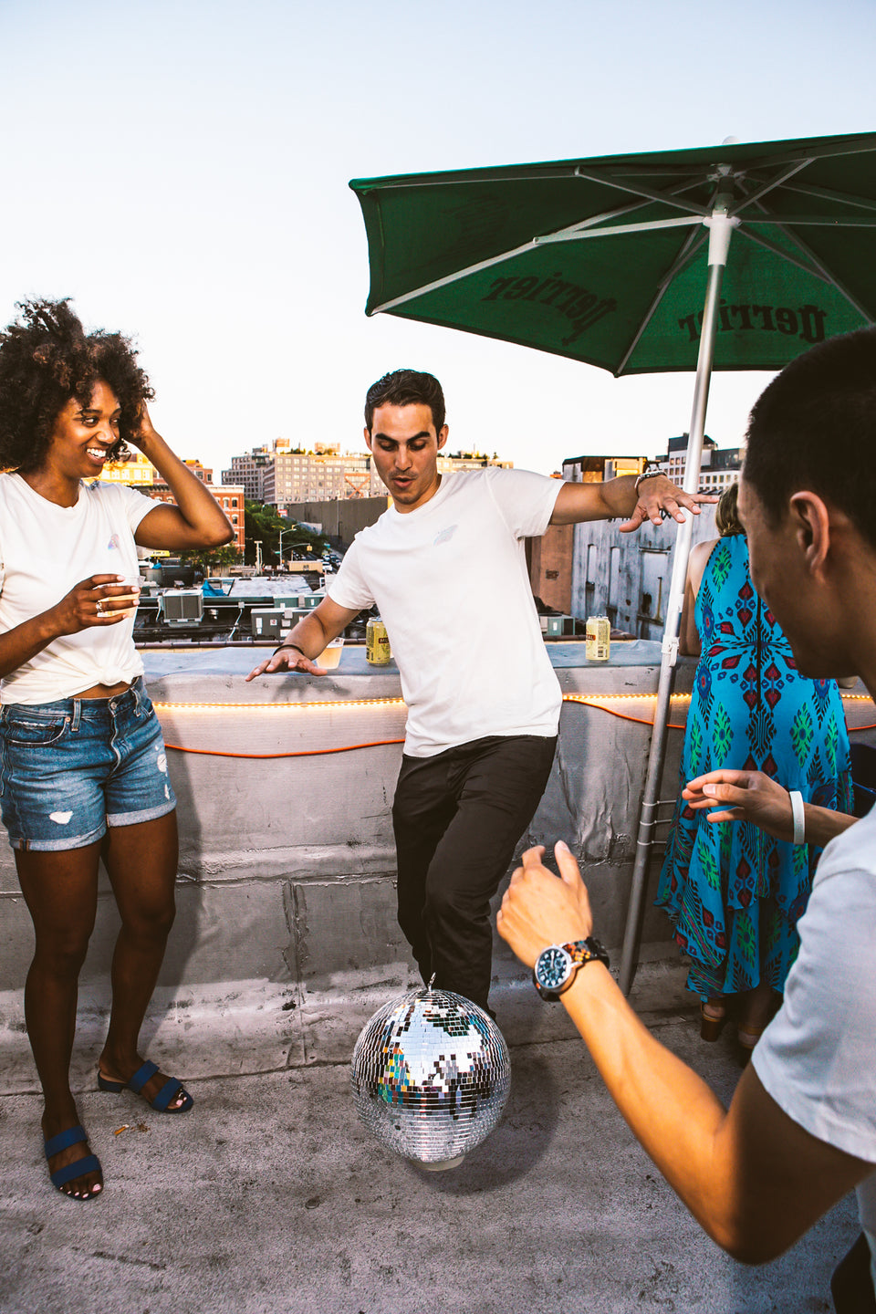 Male and female model wearing a Thousand Deep Planet Disco iridescent white shirt. Male model is balancing a disco ball on top of his foot while the female model watches in excitement. Photo taken on rooftop at Lightning Society in Brooklyn, New York