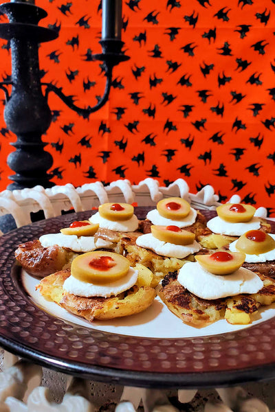 Welcome to Day 1 of Halloween Treats Week, 2019! Today I'm bringing you this hauntingly delicious Halloween Potato Eyes, or smashed creamer potatoes dressed up with goat cheese, olive slices, and Sriracha eyes.