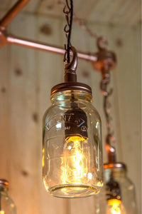 Hanging Mason jars in an 'X' formation with chains and vintage light bulbs in copper