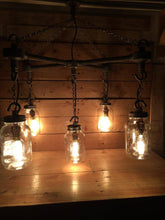 Load image into Gallery viewer, Hanging Mason jars in an 'X' formation with chains and vintage light bulbs in black