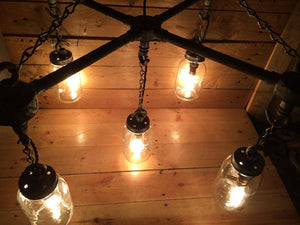 Hanging Mason jars in an 'X' formation with chains and vintage light bulbs in black