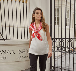 Model walks with Sésam queen foulard rouge and rose silk twill scarf around neck