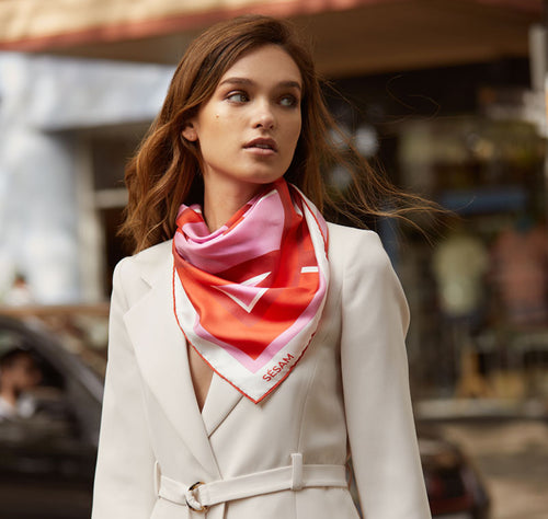 Model walks across street with Sésam modernist femme silk twill scarf around neck