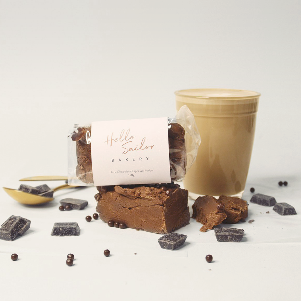 Dark Chocolate and Espresso Artisan Fudge in Hello Sailor Bakery Packaging in front of a flat white and surrounded by dark chocolate