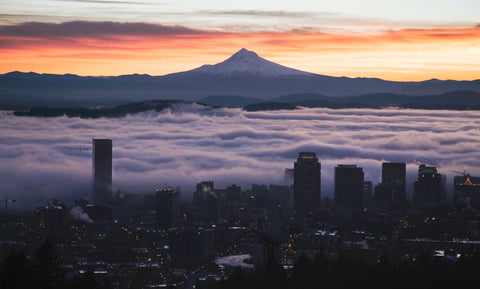 Cityscape view of downtown Portland with Mt Hood in background clouds