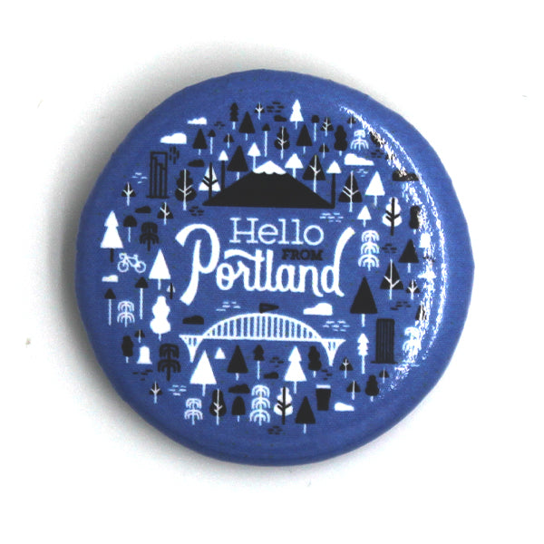 Blue Circle button with our popular Portland Pattern featuring trees, bikes, buildings, bridges and Mt. Hood. In the center it reads Hello From Portland.