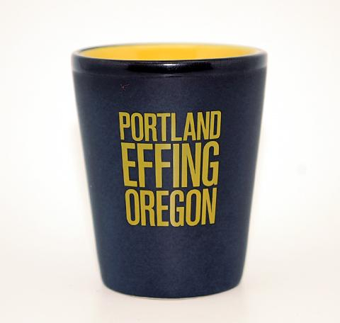 "Matte black shot glass with the words ""Portland Effing Oregon"" written on the side in big yellow letters."