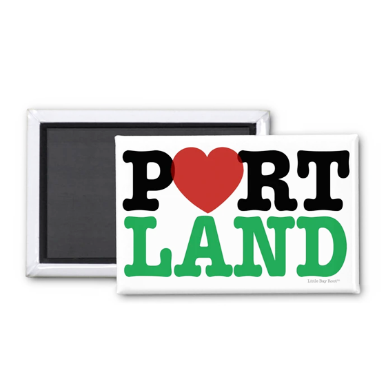 White magnet. Inside it reads Portland in the style of the I Heart NY design, with a heart replacing the O.