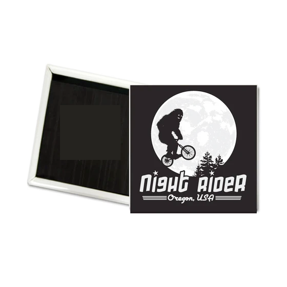 Black square magnet with sasquatch riding a bike through the air in front of the moon. Underneath it reads Night Rider, Oregon, USA.