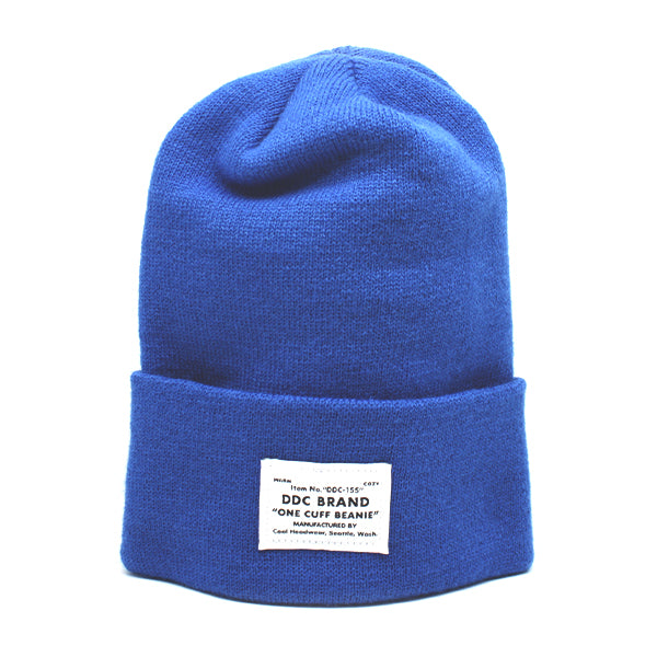 Bold blue One Cuff beanie with DDC brand patch reading out material details.