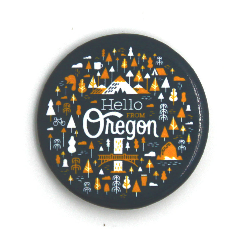 Navy Circle button with our popular Oregon Pattern featuring trees, animals, Multnomah Falls and Mt. Hood. In the center it reads Hello From Oregon.
