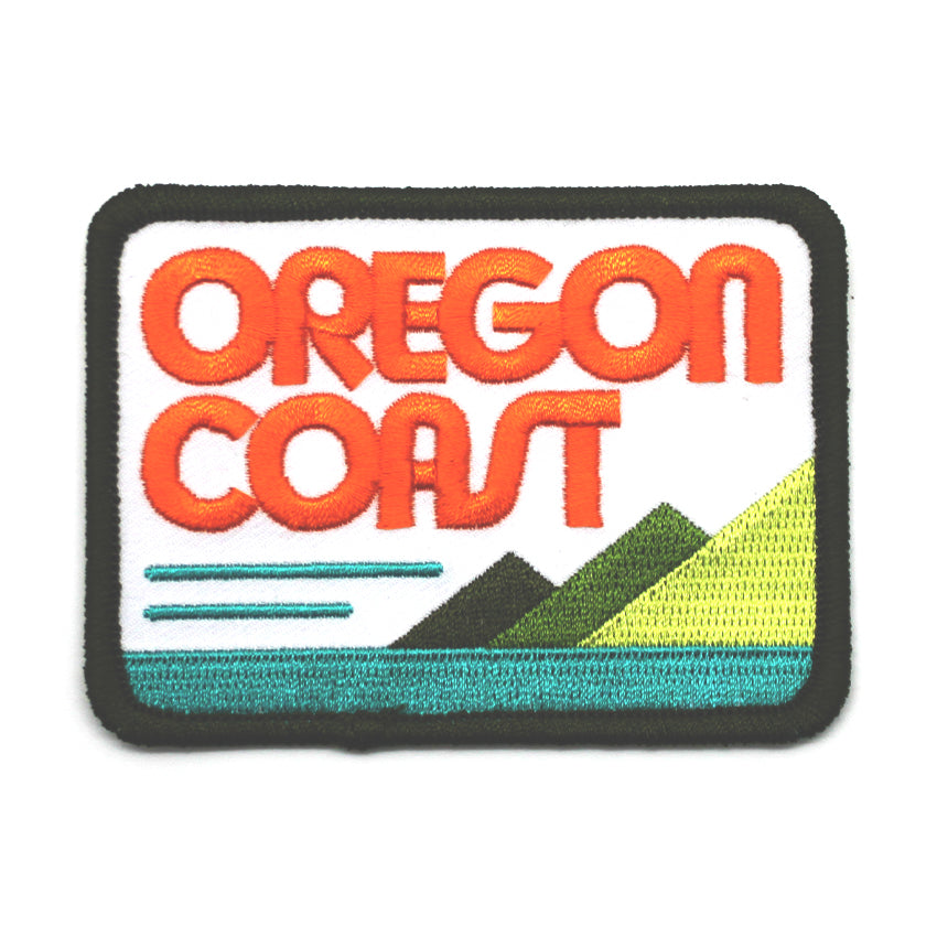 Rounded rectangle patch that shows the ocean and mountains. In large orange letters it reads Oregon Coast.