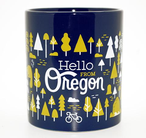 "Navy Mug with our popular Portland pattern featuring trees, bikes, rain and some of Oregons famous landmarks and creatures.. In the center is a version of our logo reading ""Hello From Oregon""."